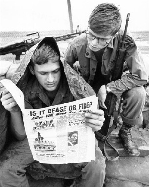 A headline with a question banners the issue of stars and stripes, the military newspaper, held by a GI of the U.S. 25th division at Cu Chi, South Vietnam on Sept. 10, 1969. The question asked is if there is a cease fire or not and if there is, whether it will be prolonged after on September 11 in morning, when funeral services for North Vietnamese President Ho Chi Minh are over. The soldiers area SP-4 John Gross of Muskegan, Mich., left, and an SP-5 Keith Bloom of Minneapolis, Minn. (AP Photo/Godfrey)
