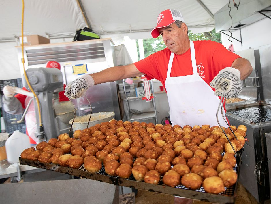 Volunteer Glenn Benoit, of Southington, carries a tray of freshly made apple fritters while working in the Zion Lutheran Church apple fritter booth Tuesday at the Apple Harvest Festival in Southington. See video at myrecordjournal.com. Dave Zajac, Record-Journal