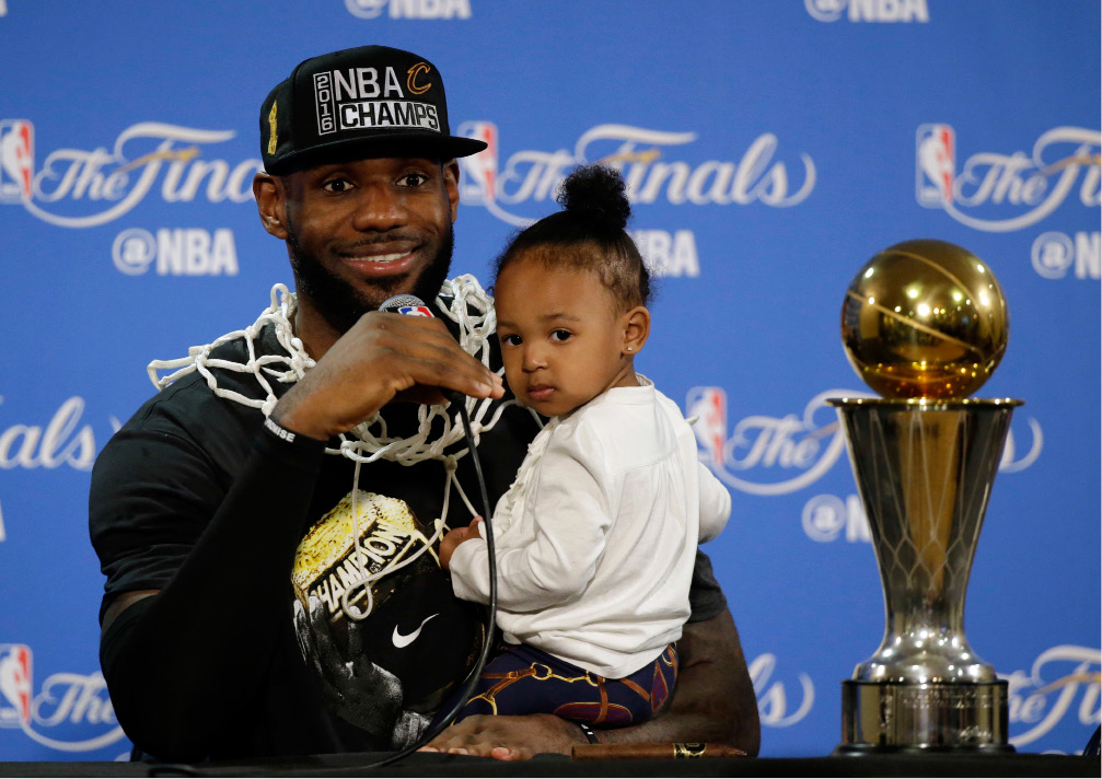 LeBron James answers questions as he holds his daughter, Zhuri, during a post-game press conference after the Cleveland Cavaliers won the NBA Finals in seven games on June 19.  On Tuesday, James was chosen as The Associated Press 2016 Male Athlete of the Year.  | Eric Risberg, file pool photo via Associated Press