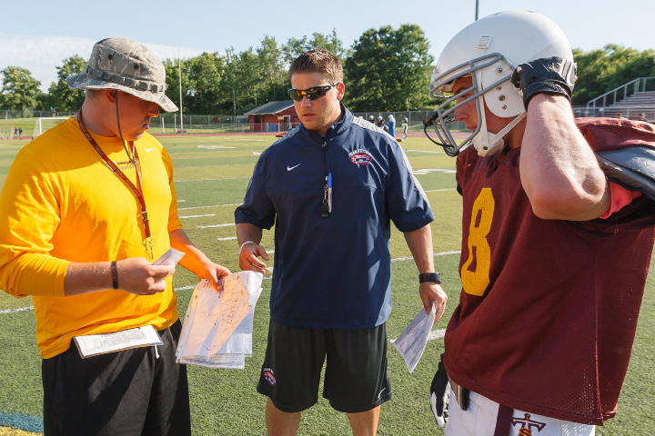 From left, Sheehan coaches Pat Miller and John Ferrazzi talk with former Sheehan standout Brandon Gauthier during practice Thursday in Wallingford for Saturday's Super 100 Classic at Rentschler Field. | Justin Weekes / For the Record-Journal