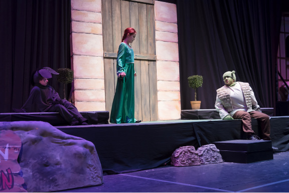 "Actors from ""Shrek the Musical, Jr.,"" from left, Tiana DiLeone as Donkey, Riley Biro as Princess Fiona, and Felipe Perez as Shrek, rehearse in costume on their set for the first time. Performances were held Friday, April 21 through Sunday, April 23 at Coginchaug Regional High School. The JLPA/PaperHouse show featured over 120 students as performers and crew, who divided into two casts and began practicing in December.