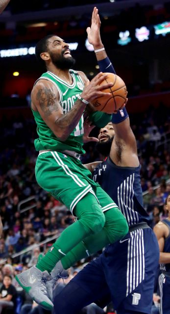 Boston Celtics guard Kyrie Irving (11) is defended by Detroit Pistons center Andre Drummond, right,while going to the basket during the first half of an NBA basketball game Friday, Feb. 23, 2018, in Detroit. (AP Photo/Duane Burleson)
