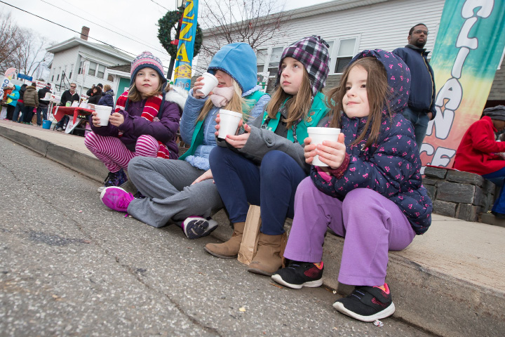 Stella Rich 7 left Sophia Rich 9 Delana Chandler 9 and Jennifer Chandler 6 all of Meriden sit on the curb to enjoy hot chocolate Saturday during Christmas in the Village in South Meriden Dec. 3, 2016 | Justin Weekes / For the Record-Journal