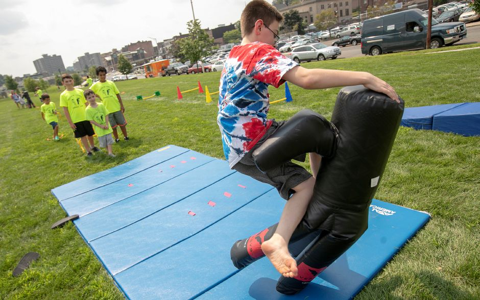 Jordan Pare, 12, of New Britain, kicks down a practice bag as a training exercise for Valentin Karate during Community Health Center's health fair on the Meriden Green, Thursday, August 16, 2018. Community Health Center, Inc. is celebrating National Health Center week with a series of fairs around the state, including Meriden's event. Valentin Karate was one of several participating vendors. Dave Zajac, Record-Journal
