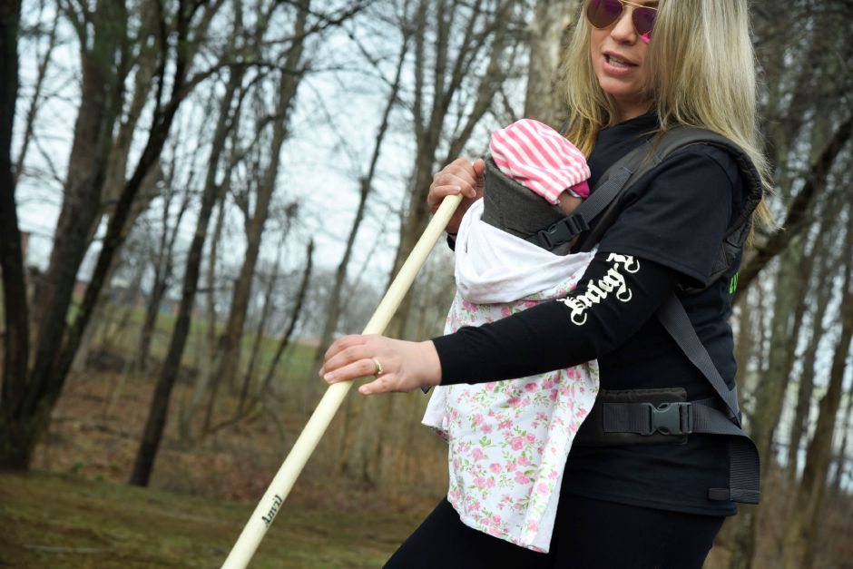 Durham resident Ashley McCarter helps rake up twigs and weeds while carrying her newborn, at Allyn Brook Park, 50 Pickett Ln., on Saturday, April 6, 2019. | Bailey Wright, Record-Journal