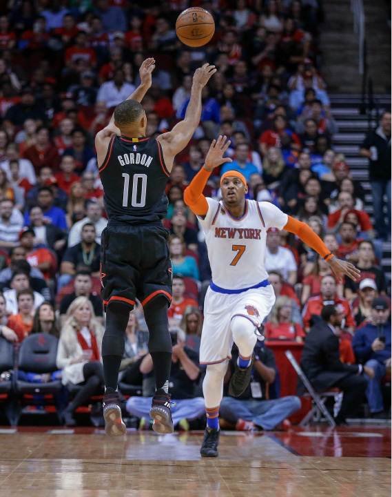 Houston Rockets guard Eric Gordon (10) shoots over New York Knicks forward Carmelo Anthony (7) during the first half of an NBA basketball game Saturday, Dec. 31, 2016, in Houston. (AP Photo/Bob Levey)