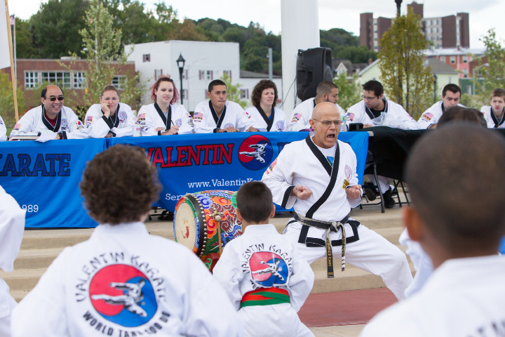 Ahmed Hernandez of Southington leads the 11am group in warm ups Saturday during Valentin Karate belt tests at the amphitheater in the Meriden Green in Meriden  Sep. 24, 2016 | Justin Weekes / For the Record-Journal