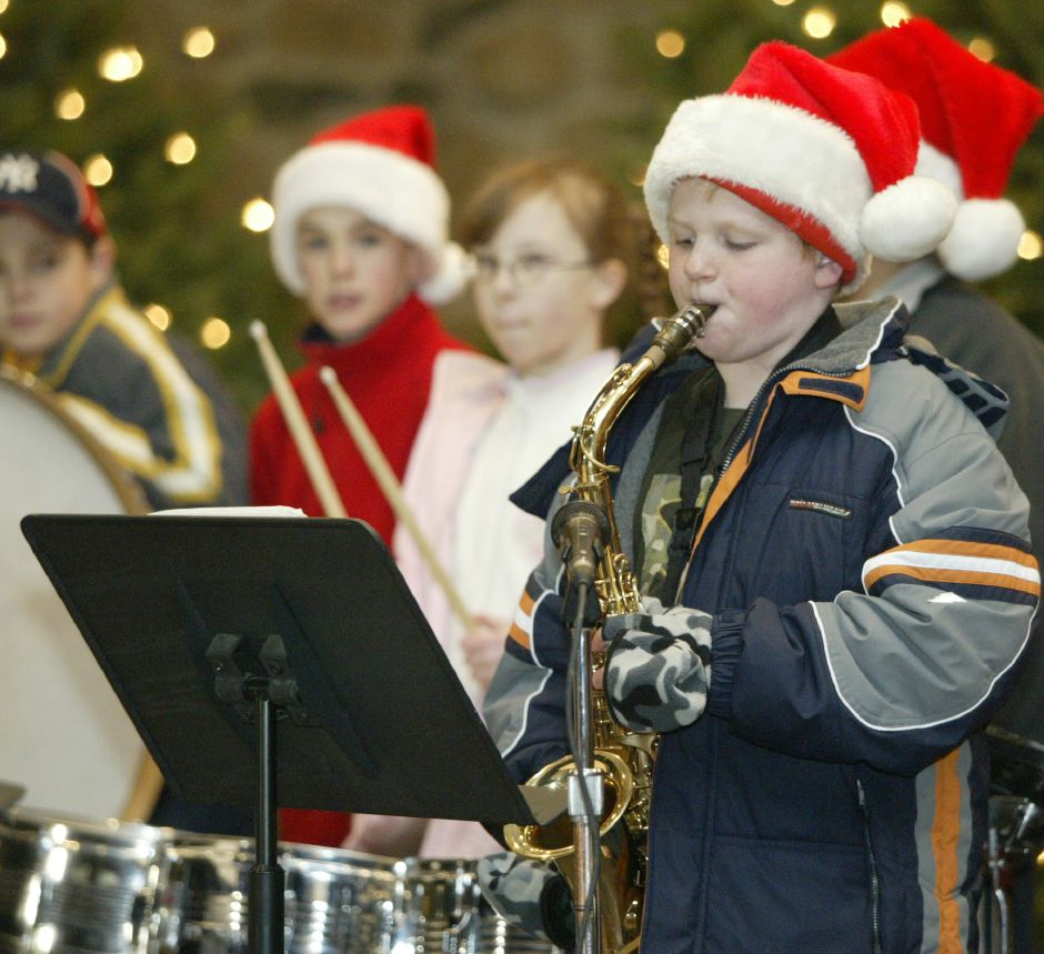 "Nate Crane, 10, a student at Ben Franklin School, plays a solo of ""O Come All Ye Faithful"" on his saxophone to entertain the crowds gathered in Hubbard Park for a Christmas festival on Dec. 12, 2006."