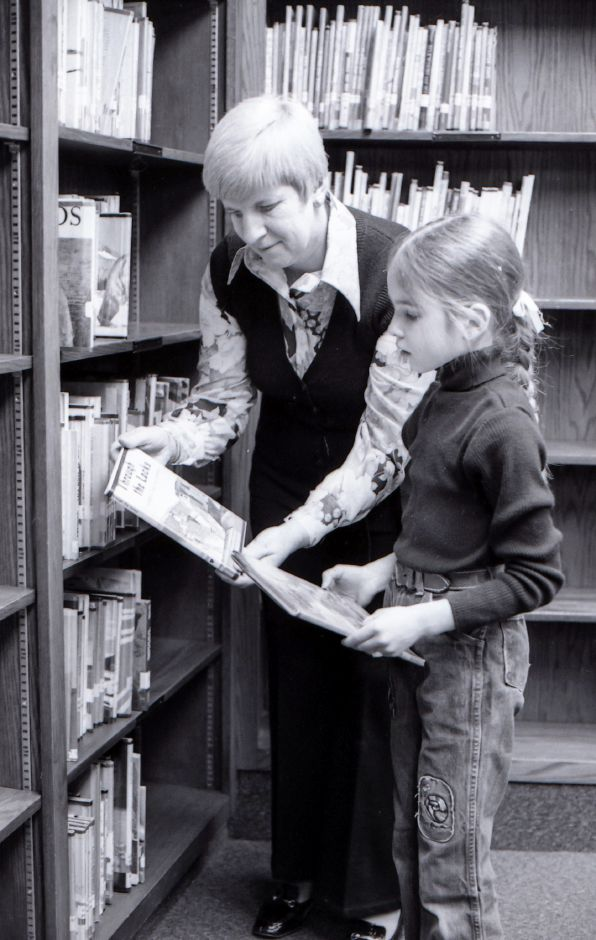 A library volunteer helps a young girl pick out a book at Pulaski School in Meriden, March 1975.