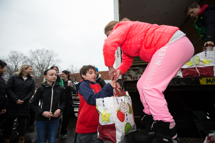 Emelie Pettit 13 hands a food bag to Nicholas Leggett 8 Sunday at Southington Community Services in Southington Dec. 18, 2016 | Justin Weekes / For the Record-Journal