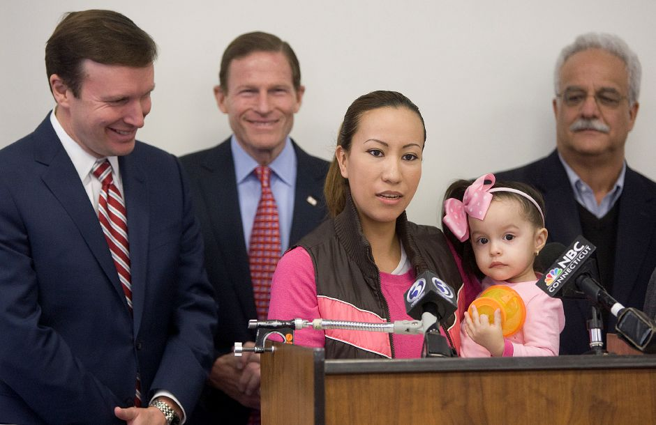 Mirella Antongiorgi, of Meriden, holding daughter, Genesis, 1, speaks during a meeting at the Meriden Public Library, Tuesday, March 31, 2015. U.S. Senators Chris Murphy and Richard Blumenthal, left, visited Meriden to discuss legislation that would create opportunities for children in low-income neighborhoods. Paul Vivian, right, interim director of Meriden Children First, also spoke during the meeting. | Dave Zajac / Record-Journal