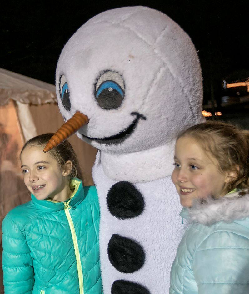 Emily Anastasio, 12, left, and sister, Katie, 9, of Meriden, pose for photos with Frosty the Snowman during Christmas in the Park at Hubbard Park in Meriden, Tuesday, Dec. 12, 2017. Dave Zajac, Record-Journal