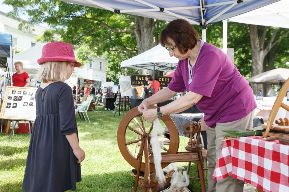 Jane Oswecki, of the Cheshire Historical Society, shows Vivian Endris, 9, how to spin wool Saturday during the 81st Annual Cheshire Strawberry Festival and Craft Fair.Photos by  Justin Weekes / Special to the Record-Journal