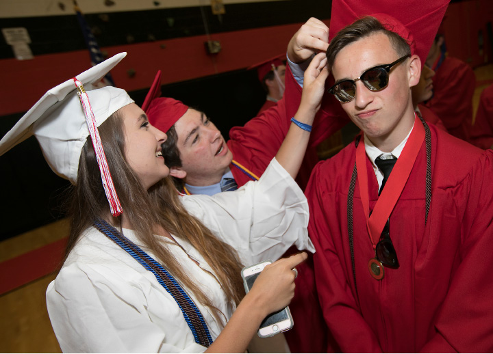 Graduate Evan Russo gets assistance with his cap prior to graduation ceremonies at Cheshire High School, Wednesday, June 14, 2017.  | Dave Zajac, Record-Journal