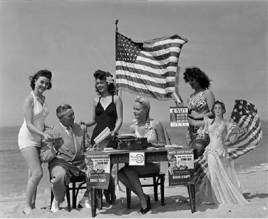 "Congressman Leyland M. Ford., R-Calif., surrounded by shapely sales girls at their beach ""office,"" is the first customer on the first day of the bond drive in Venice, Calif., Sept. 10, 1942. The young women are, left to right: Gladys Tucker; lani Nelson; Frances Brix and Bea Bryant.  The bond drive netted $51,250. (AP Photo)"