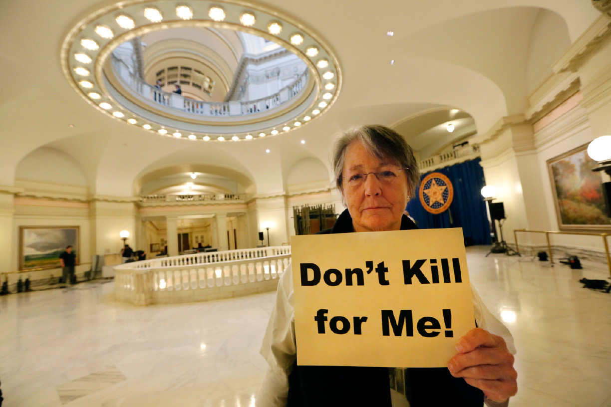 Margaret Cox with Oklahoma Coalition Against the Death Penalty holds a sign protesting the death penalty at the State Capitol in Oklahoma City, Tuesday April 29, 2014. Oklahoma prison officials halted the execution of an inmate after the delivery of a new three-drug combination on Tuesday failed to go as planned. (AP Photo/The Oklahoman, Steve Gooch)