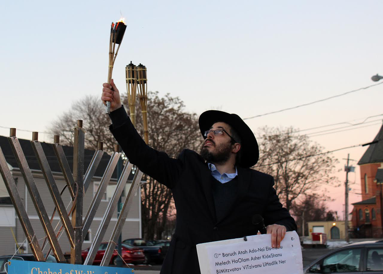 Rabbi Baruch Kaplan of the Chabad of Wallingford removes the menorah's shamash torch, used in place of candles, during a Hanukkah celebration Sunday on the Town Green in Wallingford. | Lawrence Takores