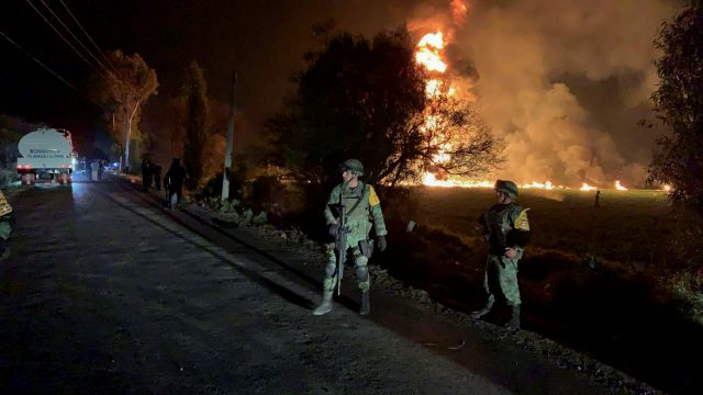 In this image provided by the Secretary of National Defense, soldiers guard in the area near an oil pipeline explosion in Tlahuelilpan, Hidalgo state, Mexico, Friday, Jan. 18, 2019. A huge fire exploded at a pipeline leaking fuel in central Mexico on Friday, killing at least 21 people and badly burning 71 others as locals were collecting the spilling gasoline in buckets and garbage cans, officials said. Officials said the leak was caused by an illegal tap that fuel thieves had drilled...