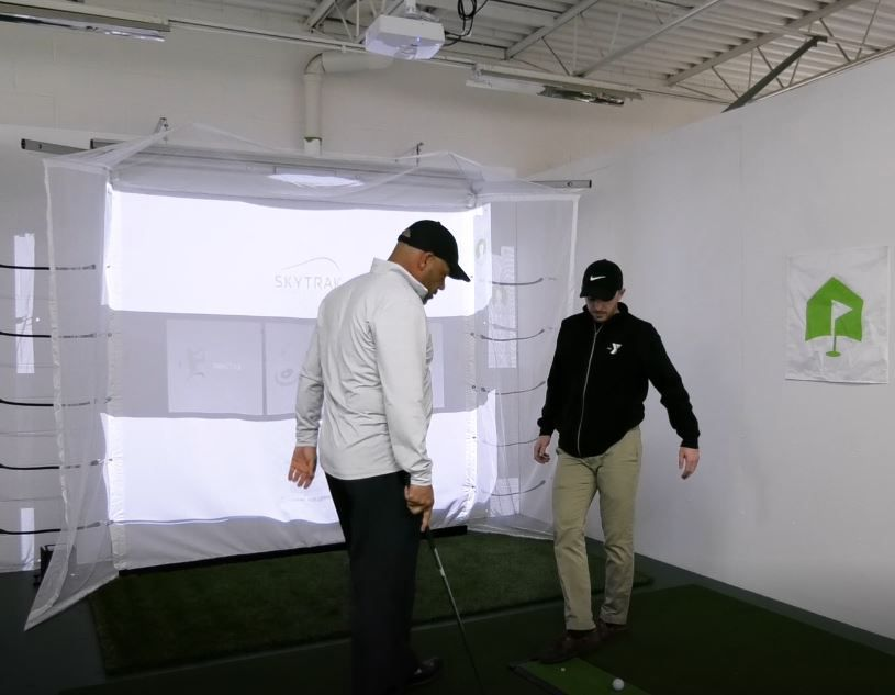 Willie Feliciano, sponsor of the new golf simulator, and Sport Director Justin Ferreira troubleshoot the program before it opens to the public at the Meriden YMCA, 110 W. Main St., Meriden. Friday, March 8, 2019. |Ashley Kus, Record-Journal