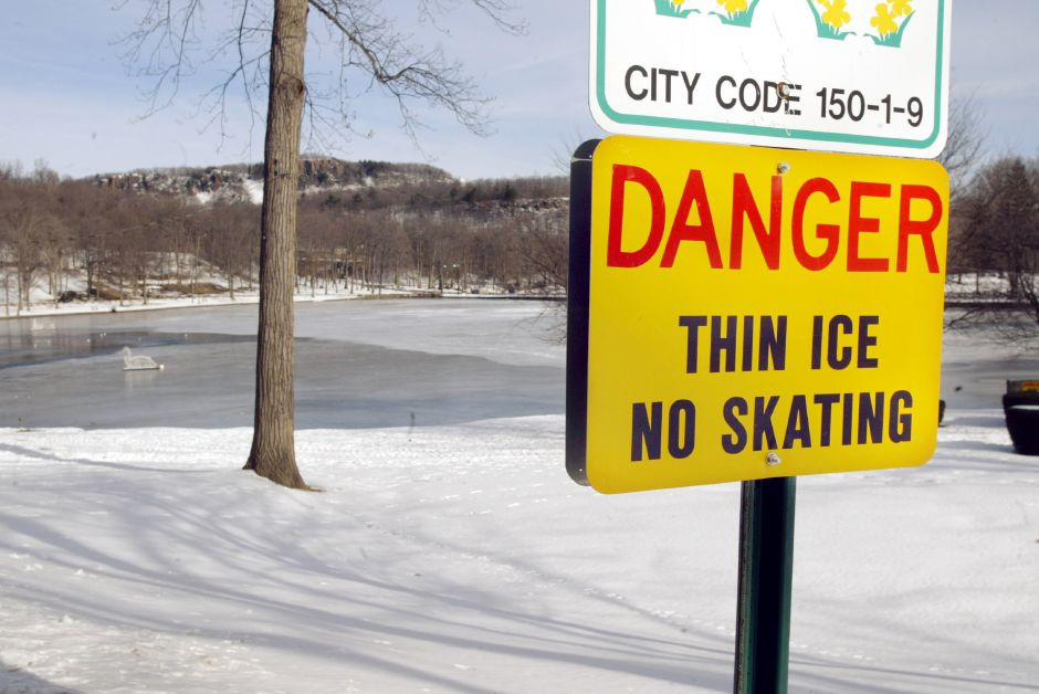 Signs along Mirror Road in Hubbard Park warn of thin ice Thurs., Jan. 16. Parks and Rec. Dept. employees monitor the lake to check for thickness of the ice.