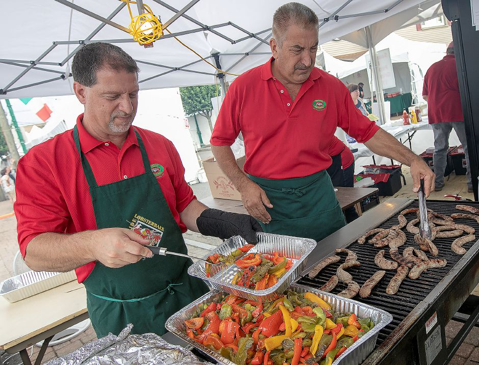 Southington UNICO members Vinnie DeSanti, left, and Bob Moffo cook up sausage and peppers during the annual Italian Festival on Center Street in Southington Friday. Dave Zajac, Record-Journal