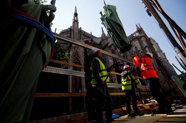 Workers secure a religious statue perched atop Paris