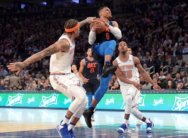 New York Knicks forward Michael Beasley, left, gets a hand on the ball as Oklahoma City Thunder guard Russell Westbrook (0) drive to the basket during the first quarter of an NBA basketball game Saturday, Dec. 16, 2017, at Madison Square Garden in New York. Knicks guard Jarrett Jack (55) looks on.(AP Photo/Bill Kostroun)