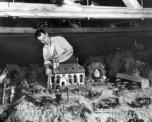 Model builder Laurence T. Gierlinger who lives near Hamburg, Pa., makes repairs to the steeple of the Shrine Church on Nov. 14, 1946. It is a replica of a memorial chapel in the Alps. He fashioned his model beautiful stained glass and has equipped it with an instrument which plays sacred music. He started the project about 43 years ago, when he was 9. He