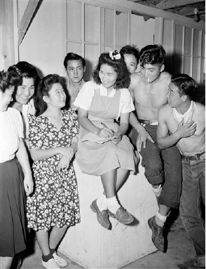 This is part of an advanced contingent of Japanese Americans evacuated from the West Coast to arrive at the Rohwer Relocation Center at McGehee, Arkansas, Sept. 21, 1942. This advanced group will get the big center ready for other West Coast evacuees. Here Agnes Uyesugi (center, bow in hair), recreation director explains to some of the boy and girls about the games they will play while in their new wartime home. (AP Photo/Horace Cort)
