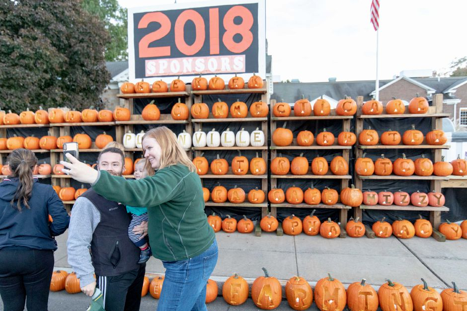 A family takes a picture in front of the pumpkin wall at the fourth annual Plainville Pumpkin Festival. The evening featured downtown streets being shut down so children could visit local businesses, as well as a band, food trucks, a haunted house and pumpkin painting. | Devin Leith-Yessian/Plainville Citizen