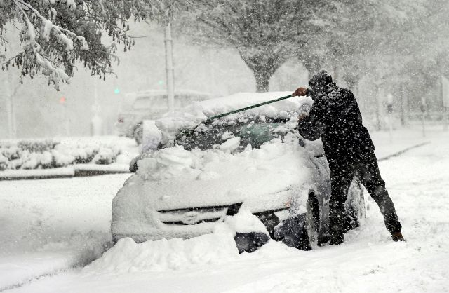 A man clears snow off of his car on State Street in Danbury, Conn., during Wednesday