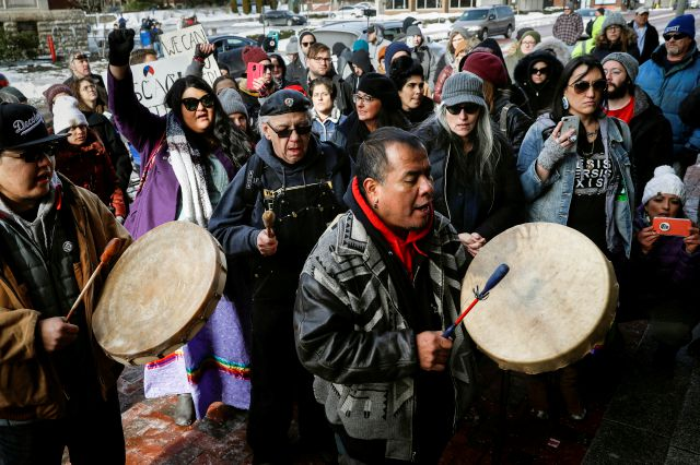 A protestor leads a Native American prayer with a traditional drum outside the Catholic Diocese of Covington Tuesday, Jan. 22, 2019, in Covington, Ky. The diocese in Kentucky has apologized after videos emerged showing students from Covington Catholic High School mocking Native Americans outside the Lincoln Memorial on Friday after a rally in Washington. (AP Photo/John Minchillo)