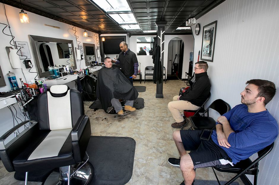While Maestri attends to Sola's haircut, customers Allan Kolesnik, of Southington, bottom right, and Peter Cambi, of East Haddam, await their turn. Dave Zajac, Record-Journal