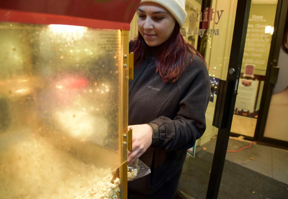 Brianna Lawrence, an employee of Serenity Salon & Day Spa, hands out popcorn outside the salon to strollers during the 9th annual Holiday Stroll in downtown Wallingford on Friday, Dec. 1, 2017. | Bailey Wright, Record-Journal