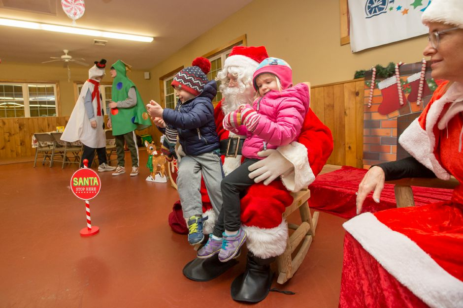 Charlie Rohman 3 left and twin sister Madeline of Southington tell Santa what they want for Christmas Saturday during Santa at Sloper hosted by the Mill Foundation at the YMCA