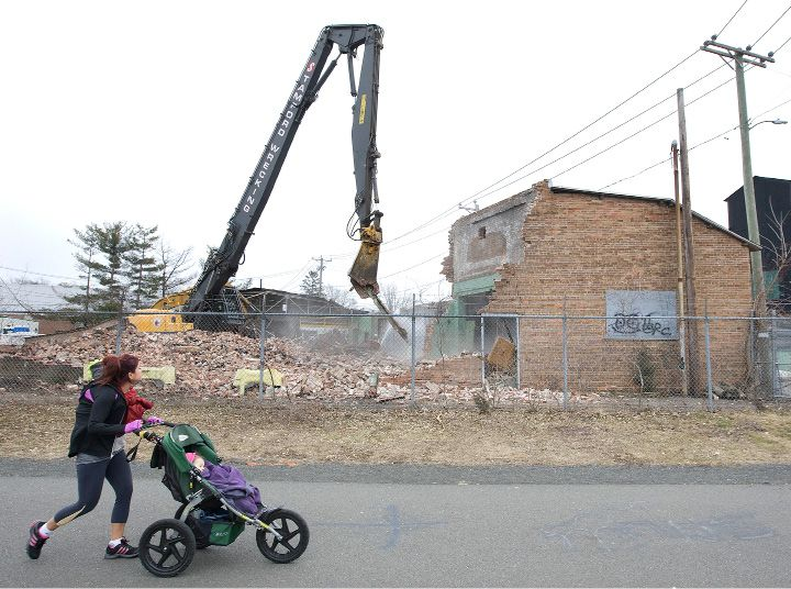 FILE PHOTO: Aviyana Picone, 1, of Southington, sleeps on a stroll with mother, Colleen, as crews demolish two former Ideal Forging buildings on High St. near the linear trail in Southington, Tuesday, March 31, 2015. Picone