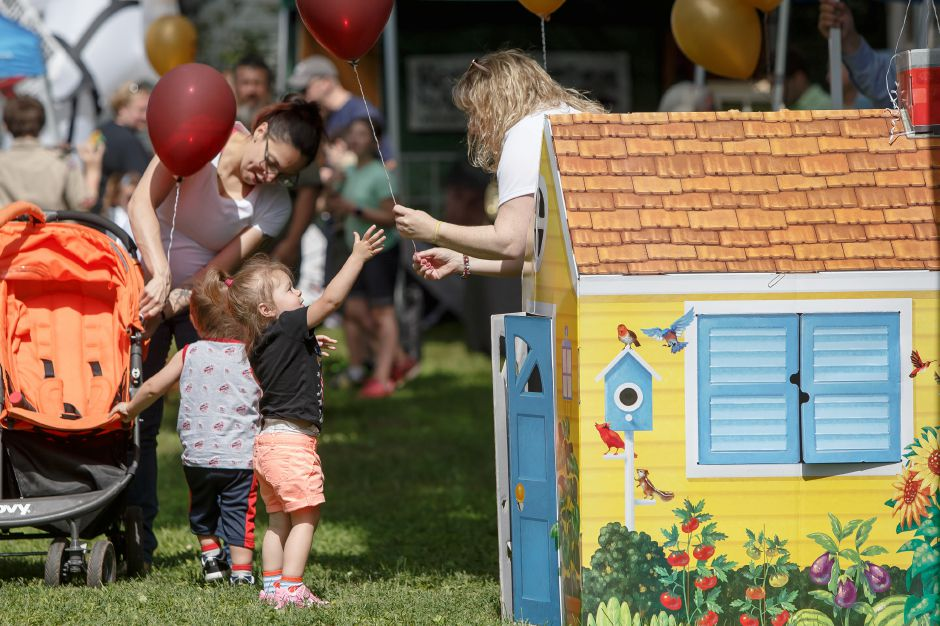 CoriAnn Alvarez 2 of Meriden gets a balloon from Julie Luchina of Cheshire Saturday during the 81st Annual Cheshire Strawberry Festival and Craft Fair on the Town Green in Cheshire May 31, 2016 | Justin Weekes / Special to the Record-Journal