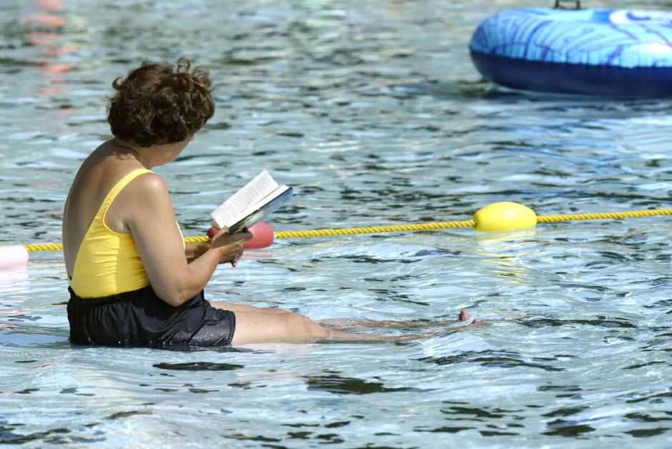 Sally Wells relaxes at the edge of Community Pool in Wallingford reading a Mary Higgins Clark novel and trying to keep cool on a hot mon. afternoon, July 15.