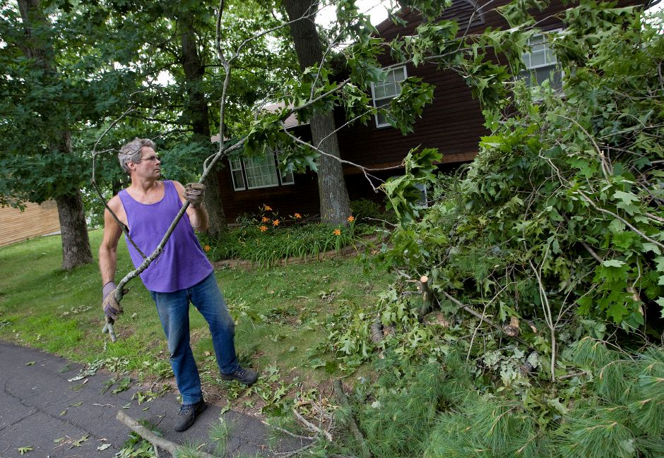 Scott Gray, of Wallingford, adds another limb to a growing pile of brush in front of his neighbors house on Oxford Trail in Wallingford, Thursday, June 25, 2015. Gray and several neighbors were still without power as of Thursday afternoon. | Dave Zajac / Record-Journal