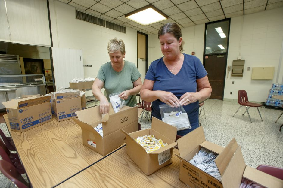 Michele Tarantino left and Karen Blakeslee both of Wallingford put together utensil packages for volunteers in the cafeteria Friday at Sheehan High School in Wallingford July 6, 2018 | Justin Weekes / Special to the Record-Journal