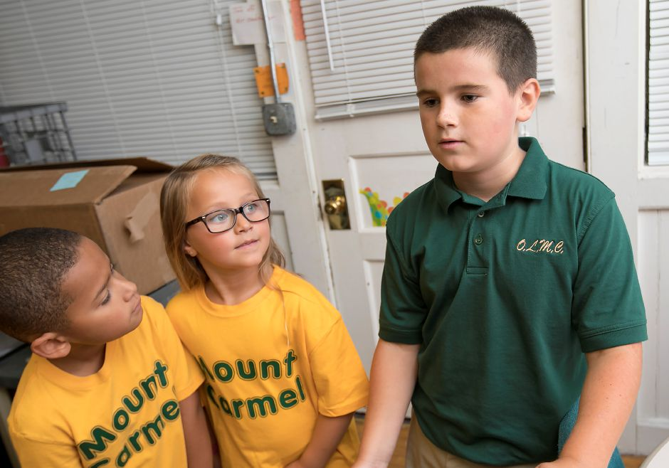 Conner Nettleton, 10, a former St. Joseph School student, talks about the transition to Our Lady of Mount Carmel School next to first-grade students, Malachi Felton, 6, left, and Gianna Boscarino, 6, Wednesday, August 30, 2017. | Dave Zajac, Record-Journal