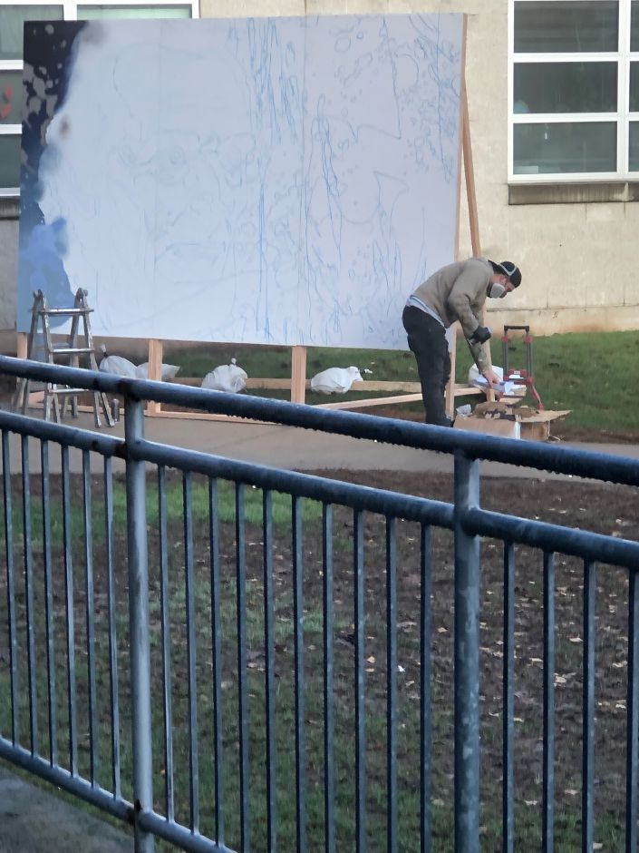 "Ryan  ""ARCY"" Christenson selects his spray paint for an art mural of former President Abraham Lincoln at Lincoln Middle School. photo by Rachel Ash"