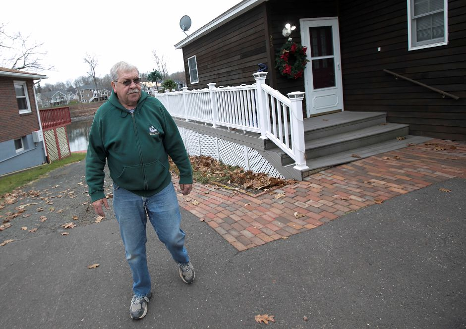 Larry Lacz, of Middlefield, walks next to his home at 23 Lakeview Place on Friday. Lacz and several neighbors are concerned that their small privately owned water company, Rainbow Springs Water System, made a request to cease operations and abandon its water system.