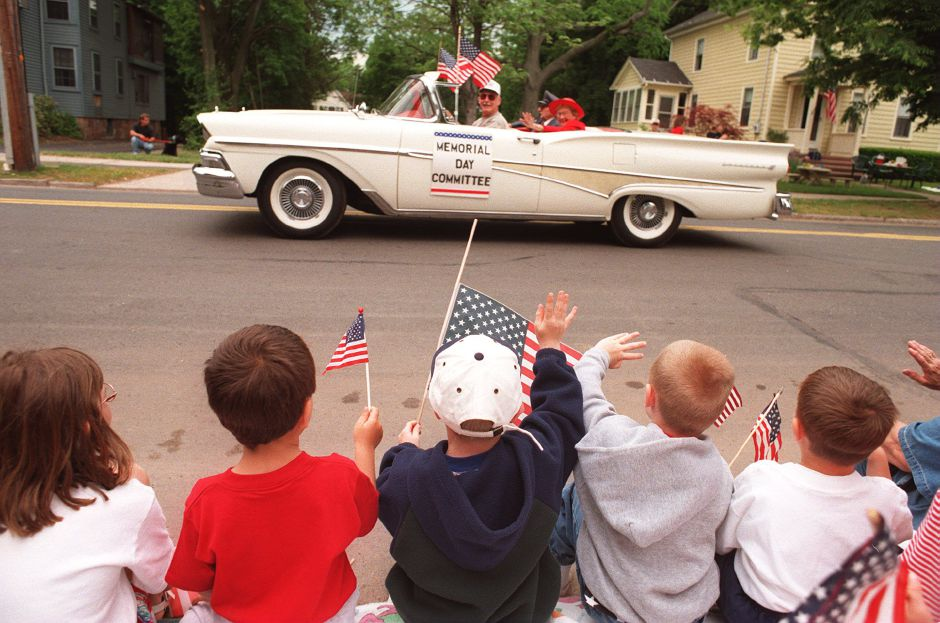 RJ file photo - One generation salutes another as flag-waving children wave to the passing Memorial Day Committee in its vintage convertible during the Wallingford Memorial Day parade May 25, 1998.