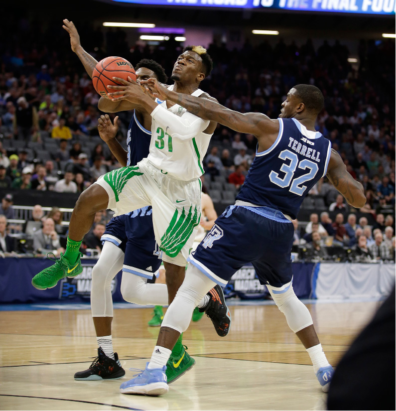 Oregon guard Dylan Ennis, left, is fouled by Rhode Island guard Jared Terrell, right, during the first half of a second-round game of the NCAA men
