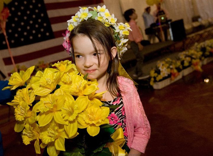 Riley Masterson, 6, of Meriden, holds a bouquet of daffodils after crowned this year