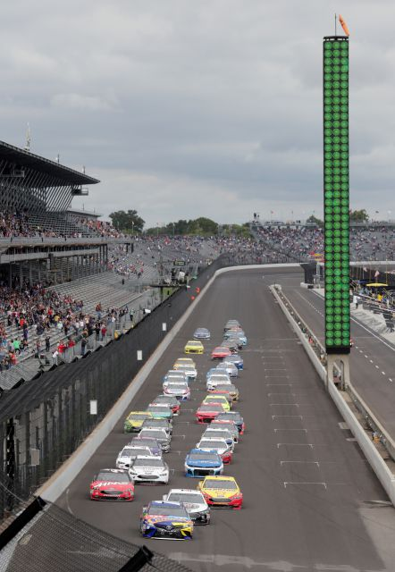 NASCAR Cup Series driver Kyle Busch (18) leads the field on the start of the NASCAR Brickyard 400 auto race at Indianapolis Motor Speedway, in Indianapolis Monday, Sept. 10, 2018. (AP Photo/Michael Conroy)