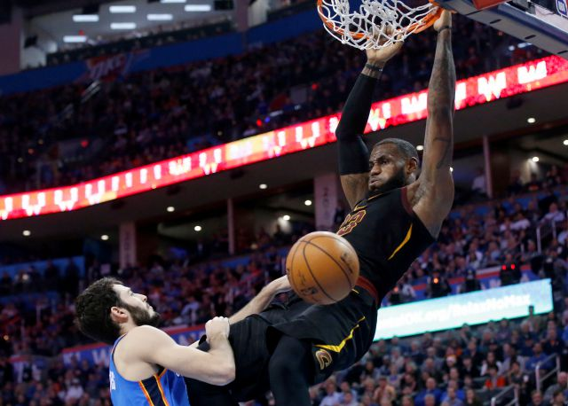 Cleveland Cavaliers forward LeBron James hangs from the basket after dunking in front of Oklahoma City Thunder guard Alex Abrines during the first half of an NBA basketball game in Oklahoma City, Tuesday, Feb. 13, 2018. (AP Photo/Sue Ogrocki)