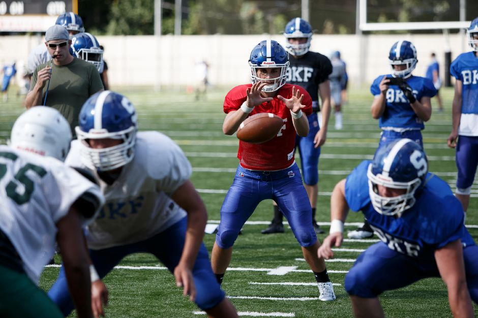 Southington quarterback Jacob Drena, above, threw an interception on his first attempt as varsity starter Friday night. He then completed 16 of his next 23 passes for 356 yards and five touchdowns to lead the Blue Knights over Glastonbury, 41-7.