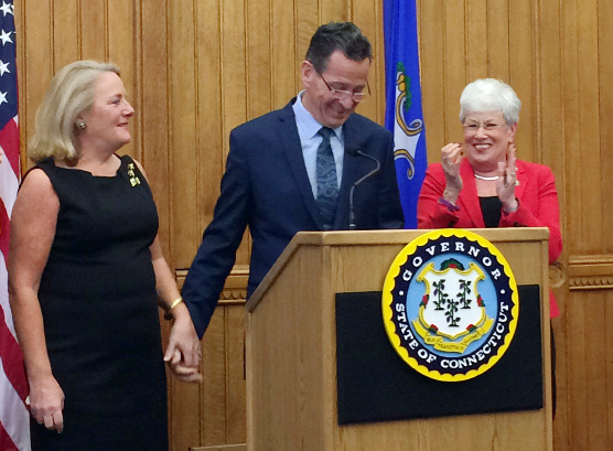 Connecticut Gov. Dannel P. Malloy holds the hand of his wife Cathy after announcing Thursday, April 13, 2017, at the Capitol in Hartford, Conn., that he will not seek a third term in 2018. Applauding is Lt. Gov. Nancy Wyman, right. (AP Photo/Susan Haigh)